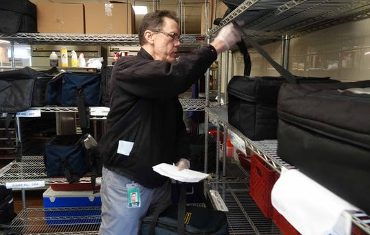 Bill Moore, a volunteer for Meals on Wheels, picks up a cooler with fresh packaged meals ready for delivery to seniors.