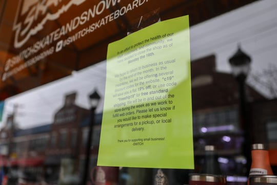 A sign hangs in the window of Switch Skateboarding in Newark, informing that the store has been closed due to the COVID-19 outbreak and urging customers to shop online.
