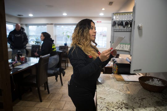 Fernanda Medina with Wolf's Elite Autos works to close up shop Monday afternoon in Wilmington. All nonessential businesses in Delaware will be closed starting at 8 a.m. Tuesday, as ordered Sunday night by Gov. John Carney.