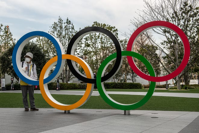A woman wearing a face mask poses for a photograph next to the Olympic rings in Tokyo, Japan.