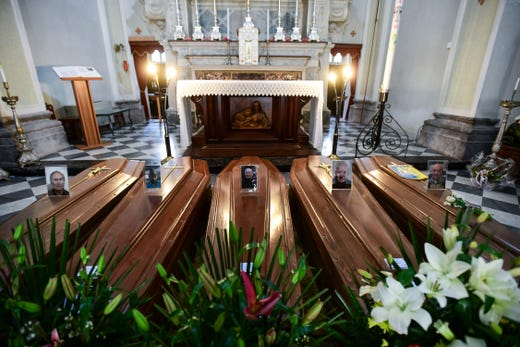 This picture taken on March 21, 2020 shows coffins on the ground of the church in Serina, near Bergamo, northern Italy.  Italy on reported 793 new coronavirus deaths, a one-day record that saw the country's toll shoot up to 4,825, the 38.3 percent of the world's totality. The total number of fatalities in the northern Lombardy regions around Milan are more than 3,000.