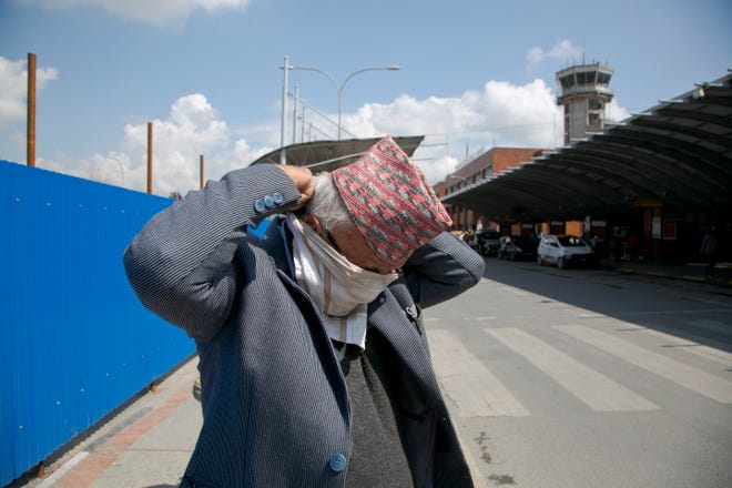 A Nepalese man covers his face with a handkerchief at Tribhuvan International airpot in Kathmandu, Nepal, March 23, 2020. Nepalese government has suspended landing permission to all scheduled international airlines carrying Nepal inbound passengers as a precaution against COVID-19. For most people, the new coronavirus causes only mild or moderate symptoms. For some it can cause more severe illness. (AP Photo/Niranjan Shrestha) ORG XMIT: XNS102