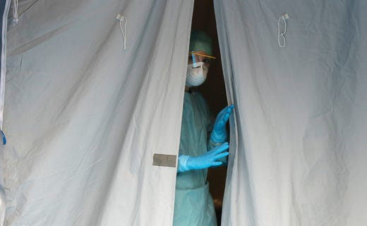 A medical staffer watches from a tent at one of the emergency structures that were set up to ease procedures at the Brescia hospital, northern Italy, Thursday, March 12, 2020. Italians woke up to yet further virus-containment restrictions after Premier Giuseppe Conte ordered restaurants, cafes and retail shops closed after imposing a nationwide lockdown on personal movement. For most people, the new coronavirus causes only mild or moderate symptoms, such as fever and cough. For some, especially older adults and people with existing health problems, it can cause more severe illness, including pneumonia.