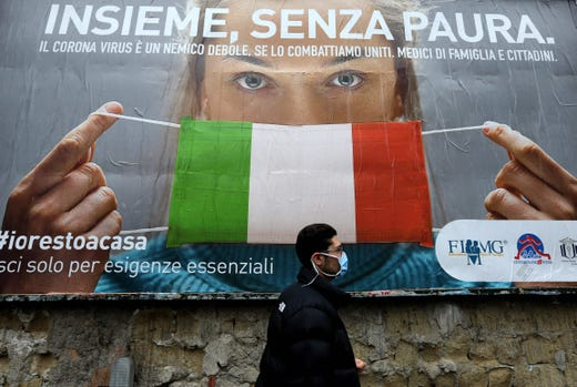 A man walks past a large billboard raising awareness to the measures   taken by the Italian government to fight against the spread of the COVID-19 (novel coronavirus) which pictures a woman wearing Italy's national flag as a face mask for protective measures and reads