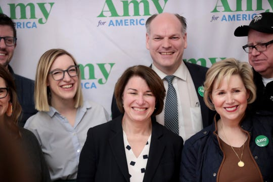 Sen. Amy Klobuchar, D-Minn., center, flanked by her husband John Bessler and daughter Abigail, poses for a picture with guests during a campaign stop in Mason City, Iowa on Feb. 2.