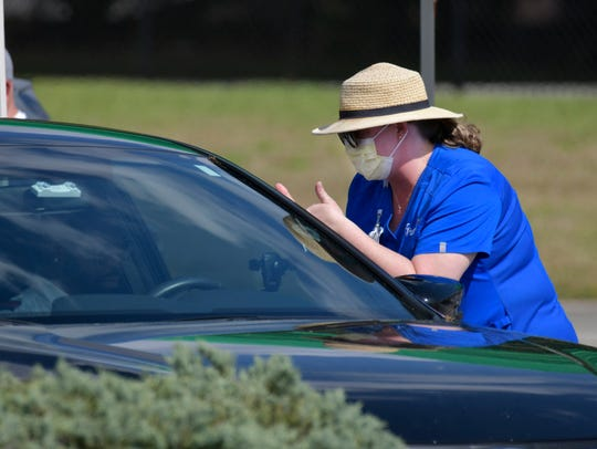 A person gets the okay to enter the mobile drive-through coronavirus testing site Friday, March 20, 2020 at the Prime Osborn Convention Center in Jacksonville, Fla.