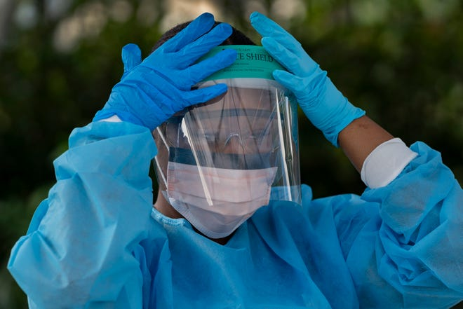 Healthcare worker Ludnie Emile prepares to test people for COVID-19 at their drive-thru coronavirus testing station in Palm Springs, Fla. on March 19, 2020.