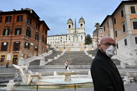A man wearing a protective mask walks by the Spanish Steps at a deserted Piazza di Spagna in central Rome on March 12, 2020, as Italy shut all stores except for pharmacies and food shops in a desperate bid to halt the spread of a coronavirus.