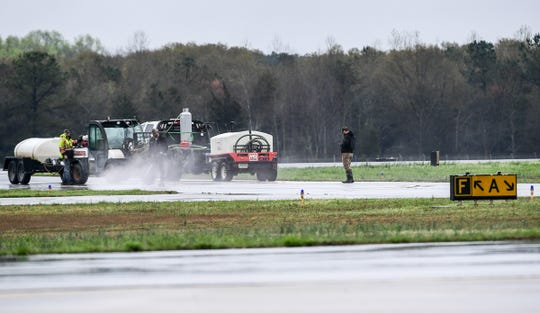 "Workers pressure wash a runway area near the Anderson Regional Airport terminal and business office in Anderson Tuesday. A sign in the window of the current business office for the Anderson Regional Airport reads ""Open for Official Business Only Due to COVID-19"" in Anderson Tuesday."