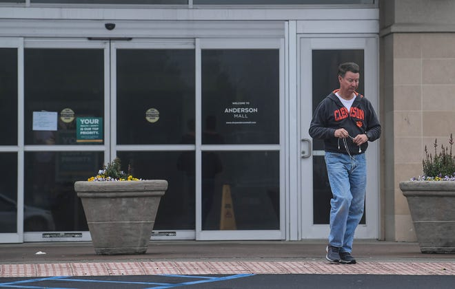 "Ken Ramsey of Anderson turns around after reading a temporarily closed sign in the window of Anderson Mall Tuesday in Anderson.  Ramsey said he walks for exercise at the city recreation center, but it is closed, and at the mall as well. The sign reads ""We Are Closed. Your Health, Safety Is Our Top Priority. Anderson Mall will be temporarily close until further notice."""