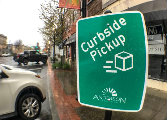 Curbside pickup signs are in front of several businesses on Main Street in Anderson.