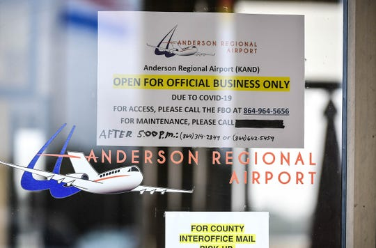 "A sign in the window of the business office for the Anderson Regional Airport reads ""Open for Official Business Only Due to COVID-19"" in Anderson Tuesday."