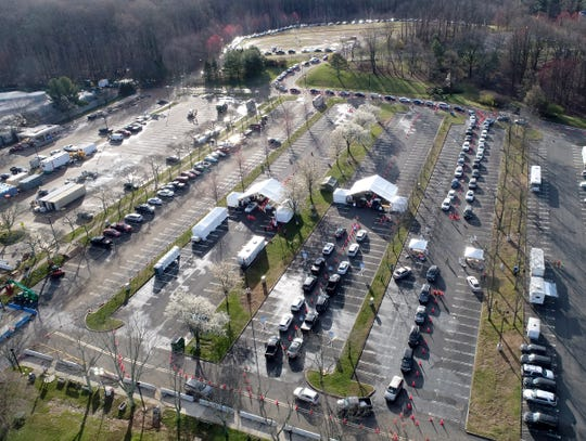 Cars snake through the parking lots at the PNC Bank Arts Center in Holmdel waiting for a Covid-19 test being done there Tuesday, March 24, 2020.