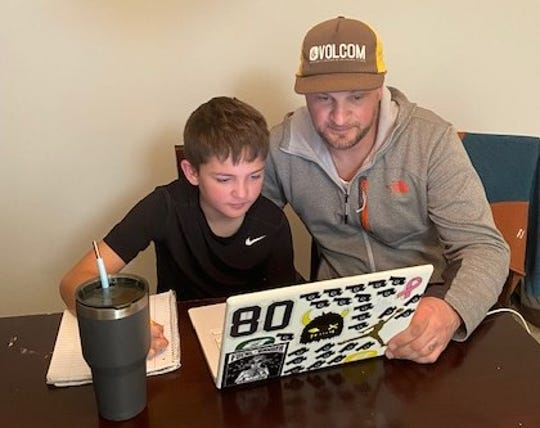 Freehold Borough substitute teacher Kane Snyder, who has been off work since March 13, helps his son, Dian, with school work. Snyder is among many school employees displaced by the switch to remote learning.