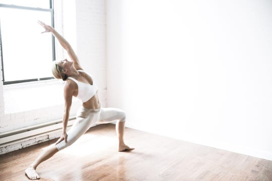 Yoga instructor Marisa Incelli, practicing in a sunlit space.