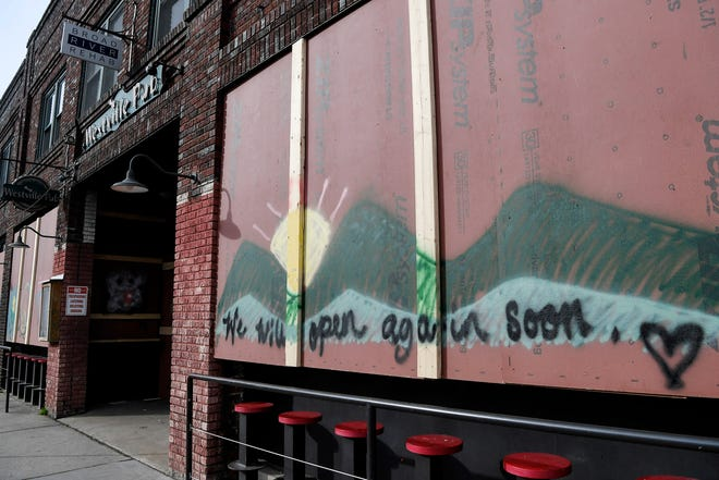 Well wishes are seen on the boarded windows of Westville Pub as the city of Asheville closes amid the coronavirus pandemic March 23, 2020.