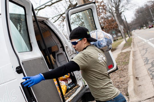 Holly Nava delivers pet food for All Species Kinship on Tuesday, March 24, 2020 in Battle Creek, Mich.