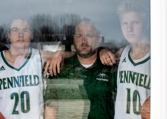 Pennfield head coach Nate Burns poses for a portrait behind a sliding glass door with his sons Gavin and Aiden Burns on Tuesday, March 24, 2020 at their home in Bellevue, Mich. Pennfield's boys varsity basketball team was bound for the district final before the MHSAA halted the season in wake of the COVID-19 epidemic.