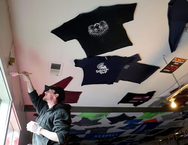 Bradley Rusk puts a coat of paint on the wall above the window in the bar of Jimmy D's in Gorst on Tuesday. Rusk was laid off from the diner temporarily after it shut down amid Gov. Jay Inslee's order for businesses to close to stem the spread of COVID-19.