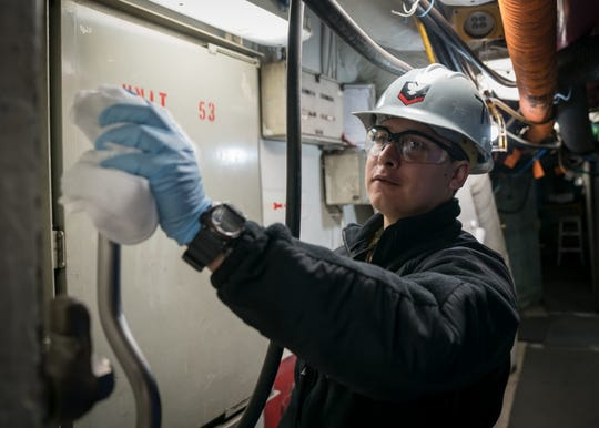 USS Carl Vinson Machinist's Mate Matt Aragon, from El Paso, Texas, sanitizes a handle on a watertight door aboard the aircraft carrier last week.