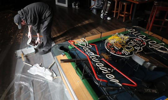Bradley Rusk pours paint into a tray as he helps spruce up the bar at Jimmy D's in Gorst on Tuesday. He's taking on side jobs after being laid off from the restaurant as he awaits his first check for unemployment.