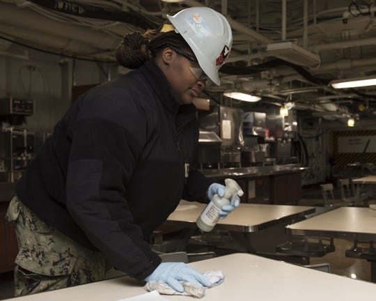 USS Carl Vinson Culinary Specialist Shequita Sexton, from Aberdeen, Miss., sanitizes tables aboard the aircraft carrier last week.