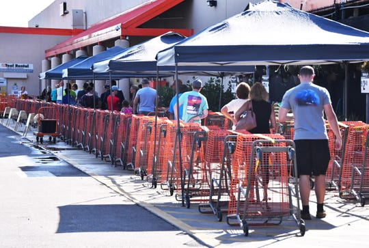The new norm, social distancing and six feet apart. People lined up at the Home Depot on Merritt Island March 24, 2020. The store was limiting the amount of customers in the store at one time and people where lined up outside waiting to shop.