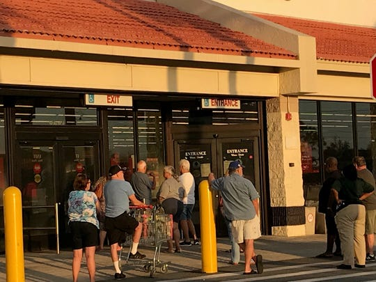 Shoppers queue up before 8 a.m. in front of the WInn-Dixie store in Port St. John, one of several stores offering special early shopping hours for customers 60 and older.