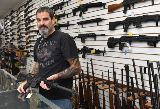 Dennis Russo, who co-owns Affordable Pawn & Gun at 1801 Post Road, in Melbourne with his wife, Yvette, has seen gun sales greatly increasing in since the start of COVID-19 precautions, and the grocery and supply hoarding began. Here he is showing a used AR-15.