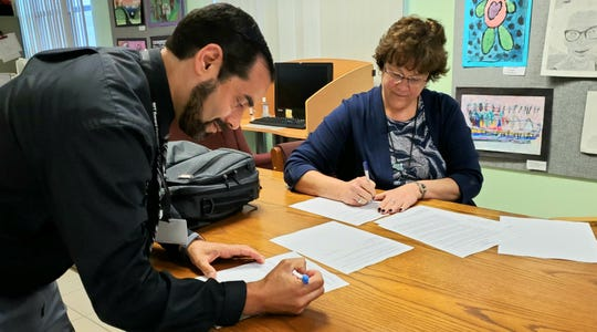 Brevard Federation of Teachers President Anthony Colucci (left) and Karyle Green, Brevard Public Schools director of labor relations, sign a memorandum of agreement on new contract terms amid the COVID-19 crisis.