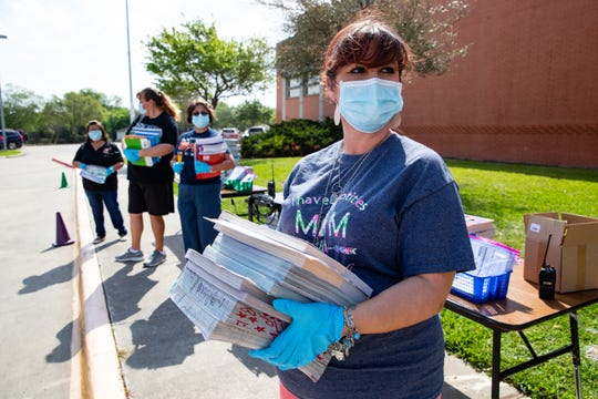First grade teacher Kristianna Andrada wearing gloves and a mask hands out school packets to parents at Oak Park Elementary School on Tuesday, March 24, 2020. The Corpus Christi Independent School District has been temporarily closed due to the COVID-19 outbreak across the United States.