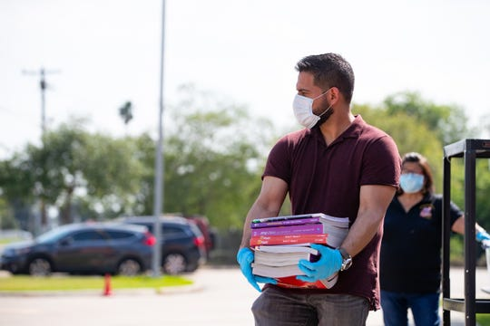 Faculty members at Oak Park Elementary School wearing gloves and a mask hands out school packets to parents on Tuesday, March 24, 2020. The Corpus Christi Independent School District has been temporary closed due to the COVID-19 outbreak across the United States.