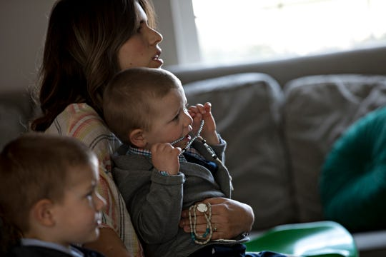 Lara Gigandet watches a live-streamed Mass while holding her two-year-old, Thomas, on Sunday, March 22, 2020. The Archdiocese of Cincinnati suspended all public Masses due to the new coronavirus pandemic.