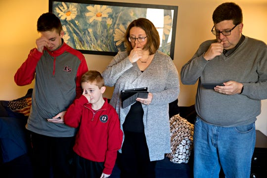 Michael Harlow and his wife, Heather, stand with their sons James, 7, and John, 14, as the Gospel is read over a live stream in their home in Colerain on Sunday, March 22, 2020. The Archdiocese of Cincinnati suspended public Mass due to the new coronavirus pandemic.