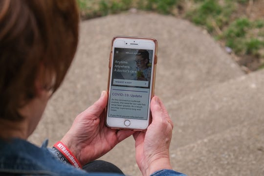 Holly Specht pulls up the application on her phone that she uses for telemedicine doctor visits from her home in Fort Thomas, Kentucky on Tuesday, March 24, 2020.