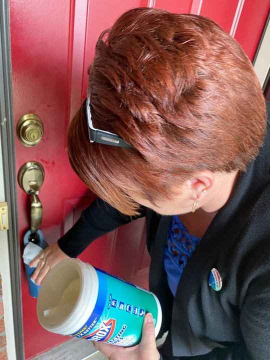 Donna Deaton, a Realtor at Re/Max Victory in Liberty Township, wipes down a front door handle with disinfecting wipes after a recent showing to help prevent the spread of the new coronavirus.