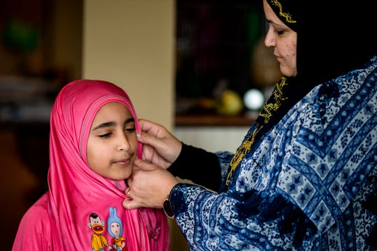 Noha Eyada fixes her daughter Sofia's isdal prayer dress before Friday prayers in their home in Mason on Friday, March 20, 2020.