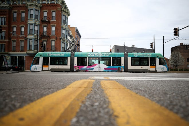 A streetcar crosses Vine and 12th streets, Tuesday, March 24, 2020, in Cincinnati's Over-the-Rhine neighborhood. Tuesday was the first day of Ohio Gov. Mike DeWine's shelter-in-place order in response to the new coronavirus pandemic. All non-essential businesses are closed and residents have been asked to stay at home.