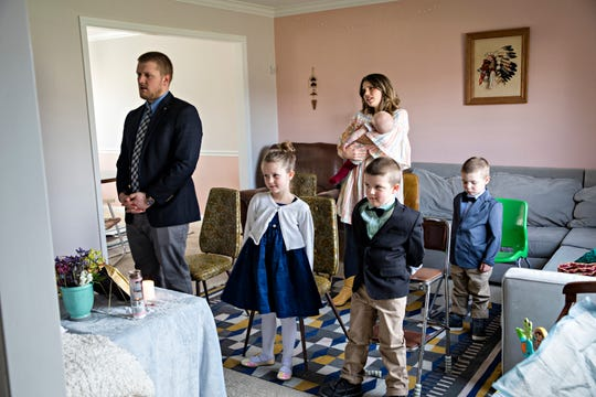 Glenn and Lara Gigandet watch a live-streamed Mass with their children Dorothy, 6, Charles, 5, Paul, 3, and Mabel, five-month-old, on Sunday, March 22, 2020, at their home in Mason. The Archdiocese of Cincinnati suspended all public Masses due to the new coronavirus pandemic.