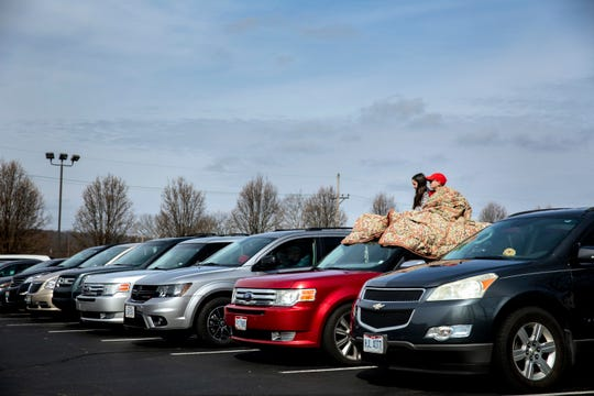 Jade Green, 11, and Cooper Navey, 10, sit on top of Janee and Andy Navey's vehicle to listen to the drive-in church service at Lindenwald Baptist Church on Sunday, March 22, 2020 in Fairfield.
