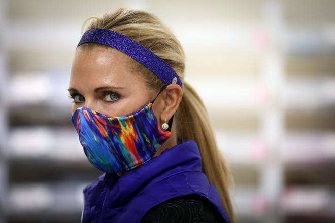 Donna Browning, founder and owner of Sweaty Bands, poses wearing one of the non-medical masks the company is planning to manufacture, Tuesday, March 24, 2020, at their offices in Fairfax, Ohio. The company is planning to repurpose a factory in Alamo, Tenn. CEO Doug Browning said he's thinking about what his customers want and how to keep his small company afloat.