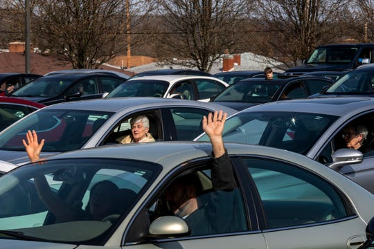Congregation members of the Lindenwald Baptist Church wave their hands outside their car windows as they sing along with the musicians at the drive-in church service in the parking lot behind Lindenwald Baptist Church on Sunday, March 22, 2020 in Fairfield.