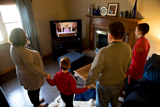 "Michael Harlow and his wife, Heather Harlow, stand with their sons James, 7, and John, 14, and hold hands as they say the ""Our Father"" over a live stream in their home in Colerain on Sunday, March 22, 2020. The Archdiocese of Cincinnati suspended all public Masses due to the new coronavirus pandemic."