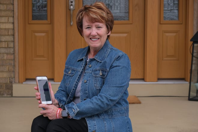 Holly Specht poses for a photo with the application on her phone that she uses for telemedicine doctor visits from her home in Fort Thomas, Kentucky on Tuesday, March 24, 2020.
