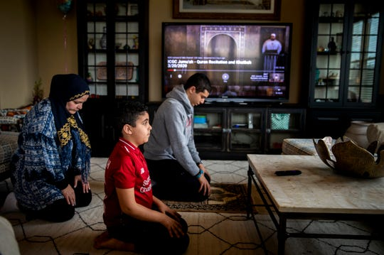 Noha Eyada prays with her children Yahia, 19, and Yusuf, 8, at their home in Mason after they watched the call to prayer from the Islamic Center of Greater Cincinnati in West Chester on Friday, March 20, 2020.