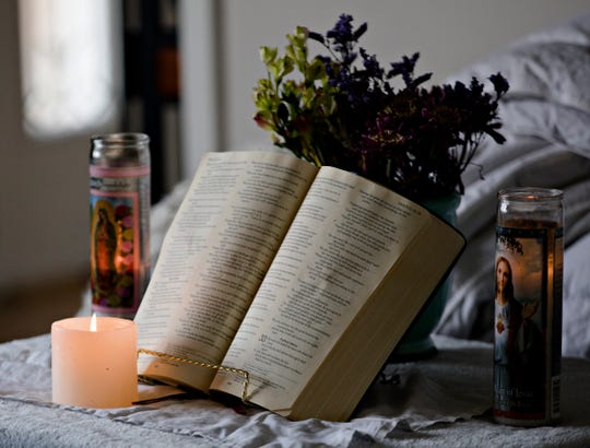 A bible is placed on a table with lit candles as Glenn and Lara Gigandet prepare to watch Sunday Mass streamed over the internet on Sunday, March 22, 2020 at their home in Mason. The Archdiocese of Cincinnati suspended all public Masses due to the new coronavirus pandemic.