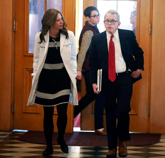 Ohio Department of Health director Dr. Amy Acton, left, and Gov. Mike DeWine walk into a coronavirus news conference Sunday, March 22, 2020 at the Ohio Statehouse in Columbus, Ohio. Gov. Mike DeWine's administration is enacting a stay-at-home order as the number of cases in the state spiked. DeWine said the stay-at-home order will start to be enforced Tuesday by local health departments and local law enforcement. (Doral Chenoweth/The Columbus Dispatch via AP)