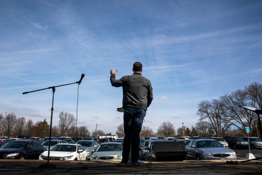 """Executive Pastor Nick Olson stands on a flatbed trailer and delivers his sermon to the congregation sitting in their cars for the drive-in church service at Lindenwald Baptist Church on Sunday, March 22, 2020 in Fairfield. Many churchgoers honked their horns to say, """"Amen."""""""