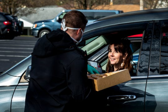Lead Pastor Tyler Green delivers donuts to Tara Olson and her family before the drive-in church service at Lindenwald Baptist Church on Sunday, March 22, 2020 in Fairfield. Volunteers also distributed activity packets for kids.