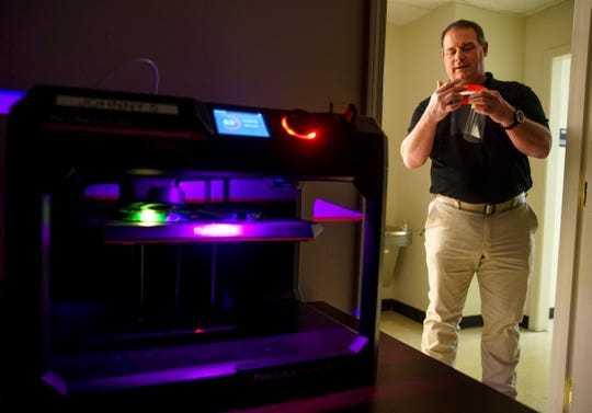 Project Director Doug Catellier adjusts a face shield on one of the 3D printed mounts while a printer works away printing additional parts at the Austin Peay GIS Center in Clarksville, Tenn., on Tuesday, March 24, 2020.